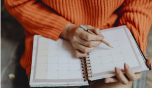 Photo of a person holding a pencil to a planner sitting on their lap